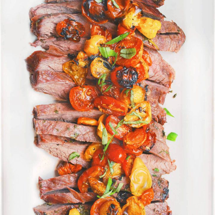 Top view of grilled flank steak cut up with roasted tomatoes on top on a white plate