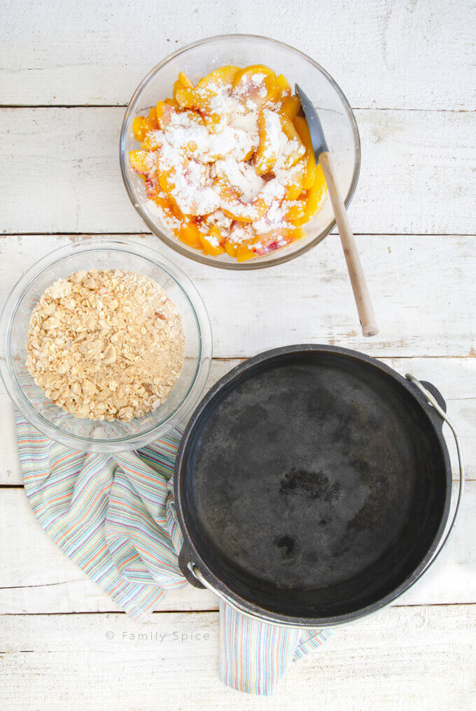 Overhead shot of making a peach crisp with almonds in a Dutch oven by FamilySpice.com