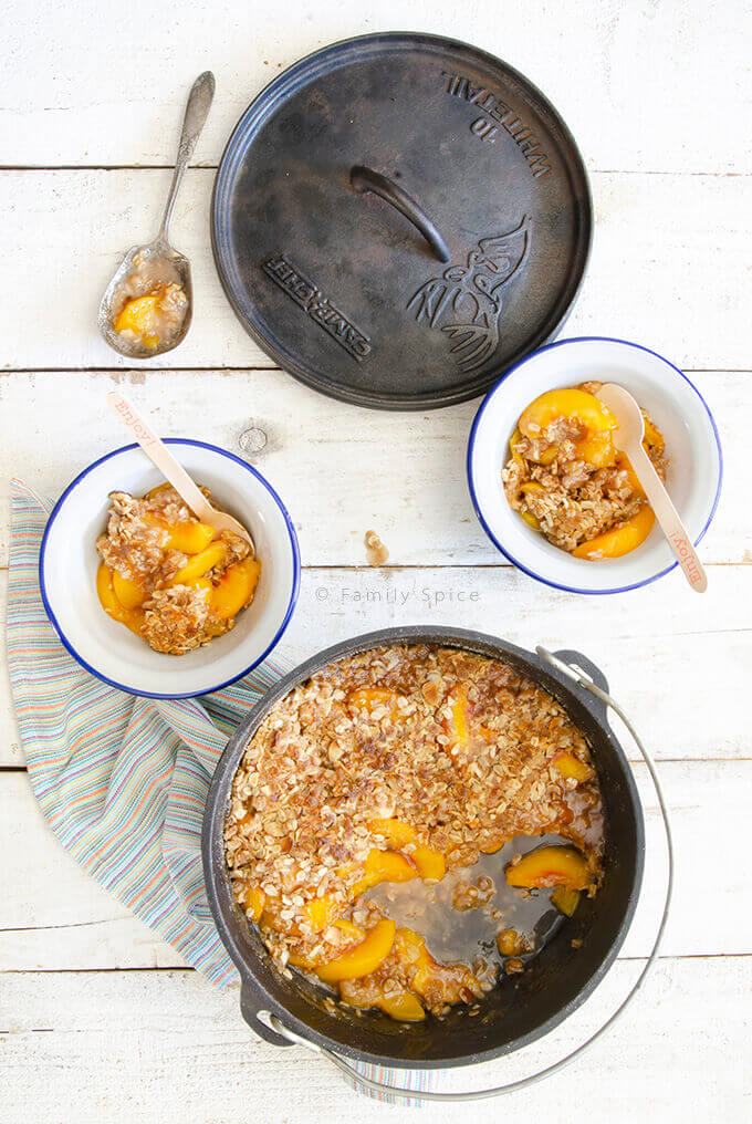 Overhead shot of peach crisp with almonds in Dutch oven and in bowls by FamilySpice.com