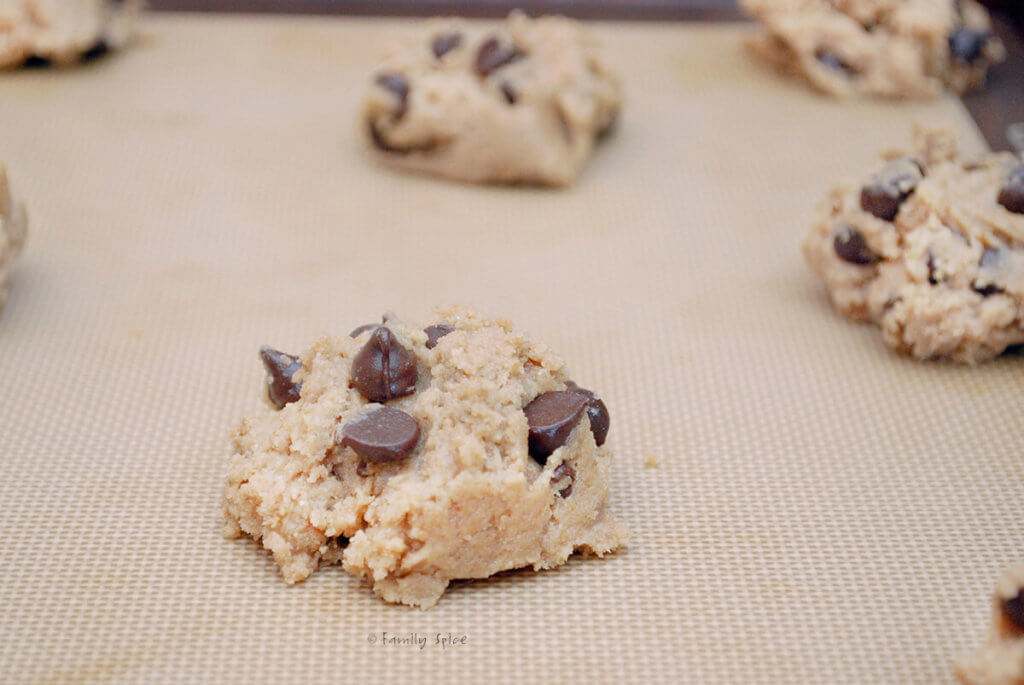 Adding raw chocolate chip cookie dough on a baking sheet lined with silicone baking mat