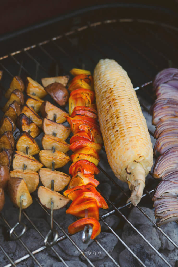 Skewered potatoes, onions, bell peppers and corn on the cob cooking on a grill