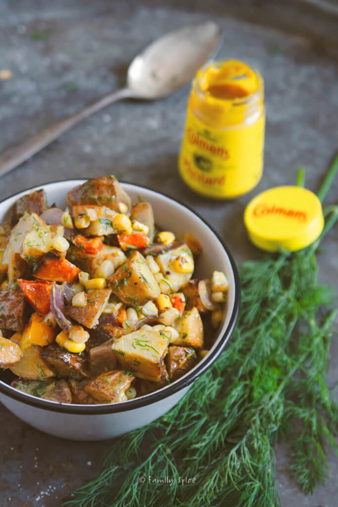 Grilled mustard potato salad in a bowl with fresh dill and a mustard bottle next to it