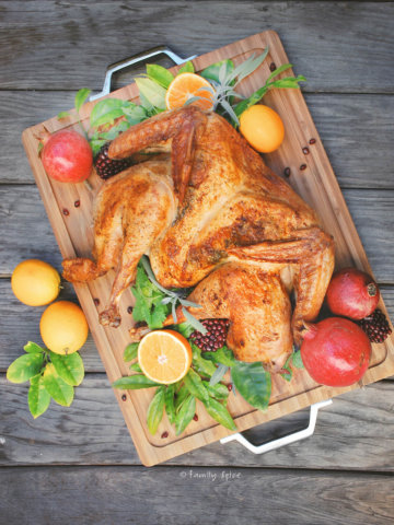 Overhead image of butterflied turkey with oranges, pomegranates and fresh herbs on a cuttingboard