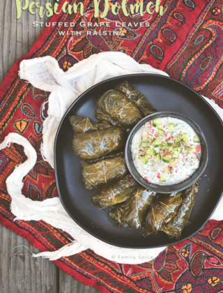 Overhead shot of a plate full of Persian dolma (or dolmeh/dolmades), stuffed grape leaves with a bowl of yogurt dip - FamilySpice.com