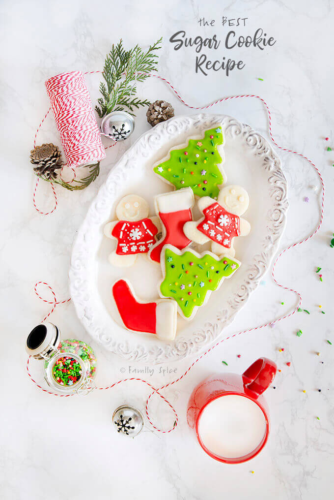 Top view of Christmas themed sugar cookies on a white plate by FamilySpice.com