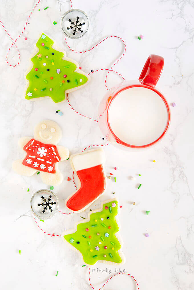 Overhead view of decorated Christmas cookies with a mug of milk by FamilySpice.com