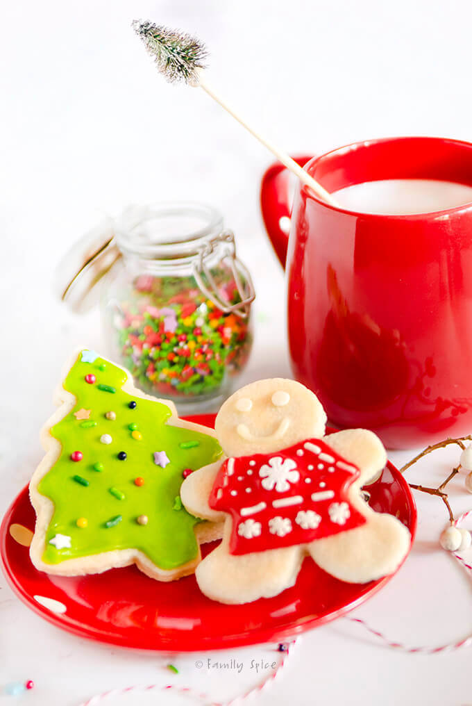 Side view of decorated Christmas cookies with a mug of milk by FamilySpice.com