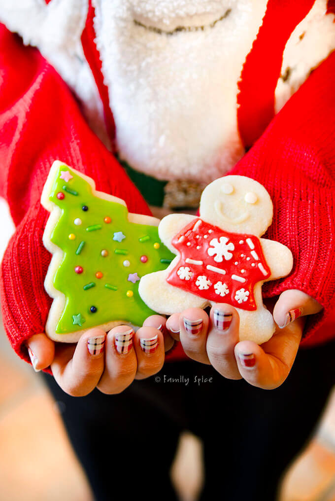 Closeup of young girl holding two decorated Christmas sugar cookies by FamilySpice.com