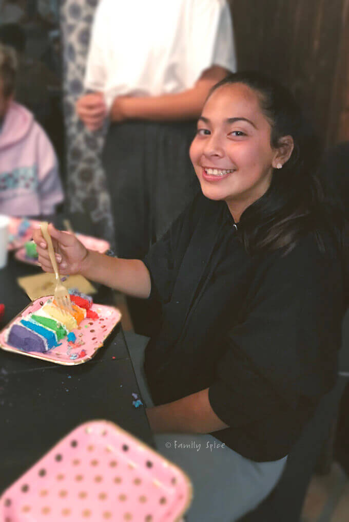 My daughter enjoying her rainbow layered unicorn cake for her birthday by FamilySpice.com