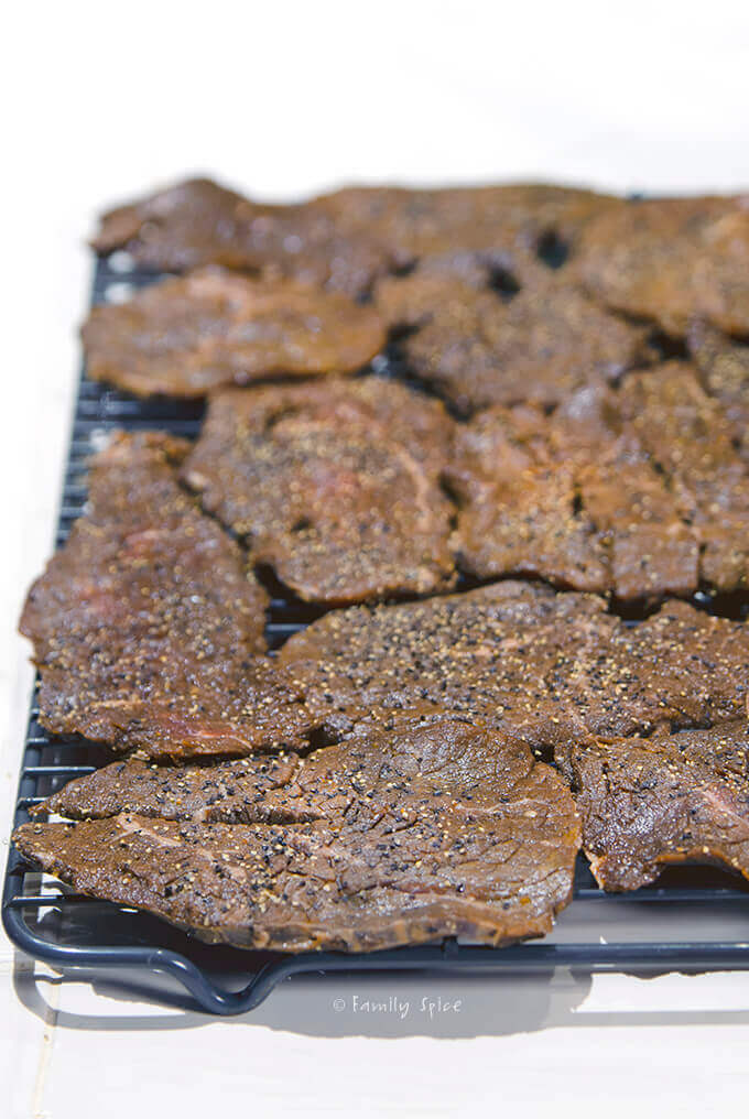 Marinated slices of meat on a rack ready to be oven dried for beef jerky by FamilySpice.com