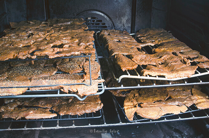 Beef jerky drying on wire racks in the oven by FamilySpice.com