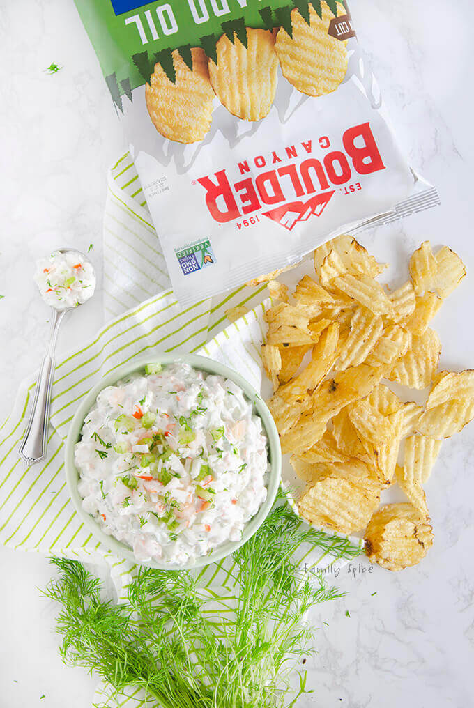 Closeup of overhead shot of a bowl of shrimp and crab dip with fresh dill and Boulder Potato Chips by FamilySpice.com