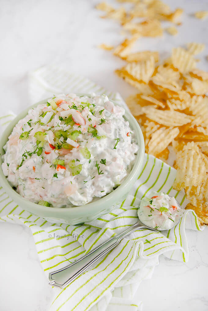 Side view of a bowl of shrimp and crab dip with fresh dill and potato chips scattered around it by FamilySpice.com