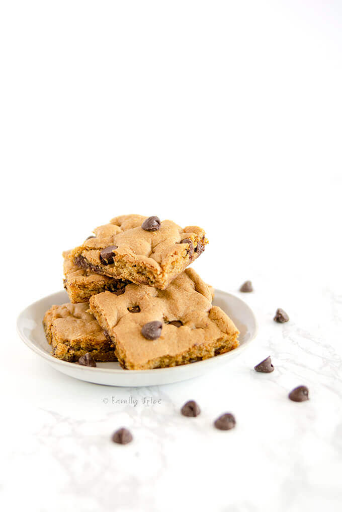 Side shot of sheet pan chocolate chip cookie bars on a white plate by FamilySpice.com