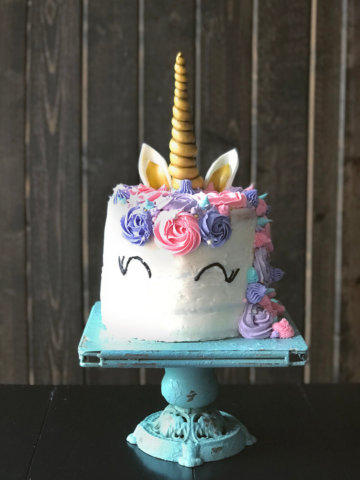 A rainbow unicorn cake frosted in white with pink and purples swirls and golden horn