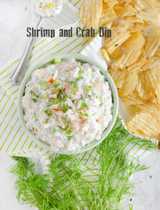 Closeup of overhead shot of a bowl of shrimp and crab dip with fresh dill and potato chips scattered around it by FamilySpice.com