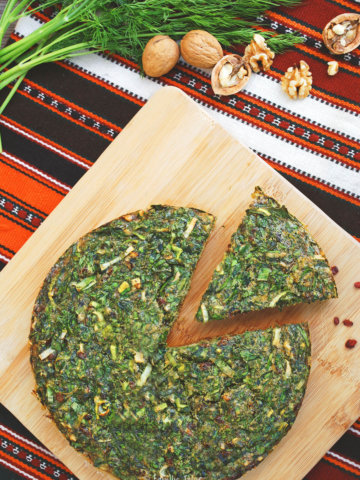 Kuku sabzi on a wood cuttingboard with a slice cut out and herbs and nuts around it