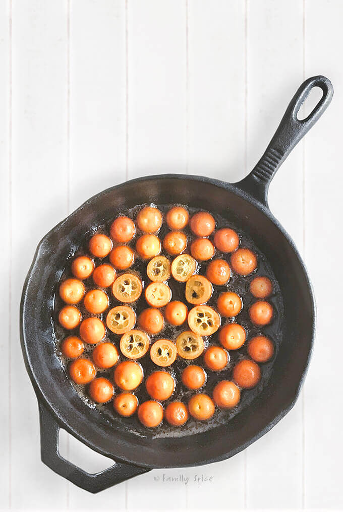 Kumquat halves lined on the bottom of a cast iron pan to make kumquat upside down cake by FamilySpice.com