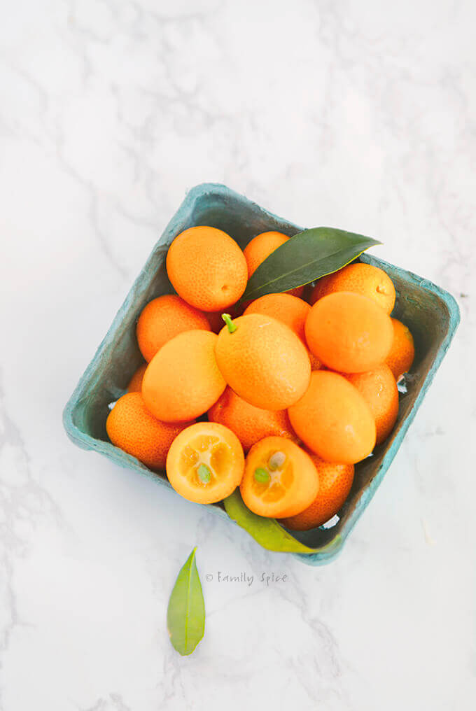 Overhead shot of kumquats in a blue cardboard box by FamilySpice.com