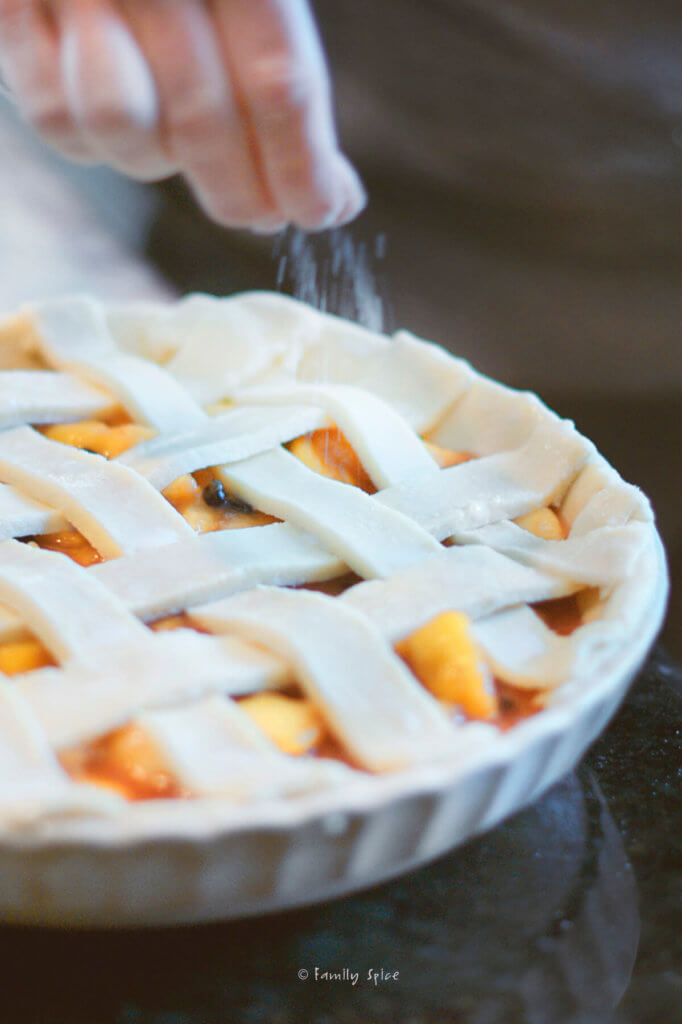 Closeup of sprinkling white sugar over an unbaked blueberry peach pie