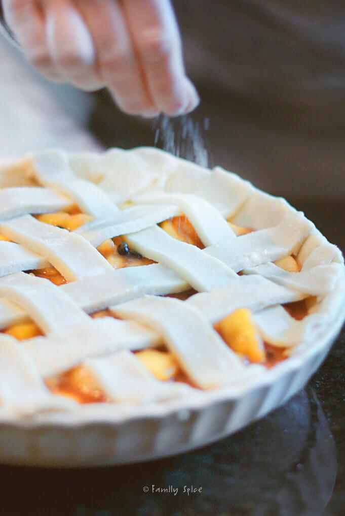 Sprinkling sugar over lattice top peach blueberry pie by FamilySpice.com