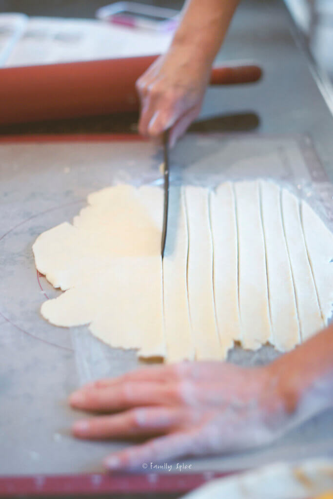 Using a knife to slice strips of pie dough for a lattice top