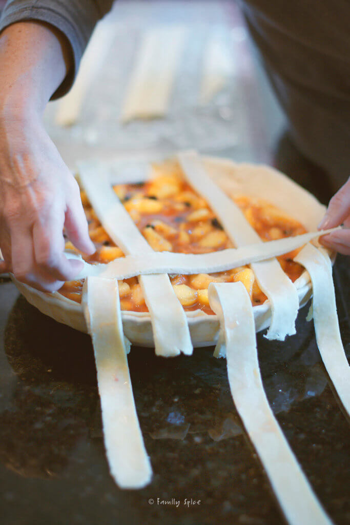 Closeup of assembling the lattice top of an unbaked blueberry peach pie