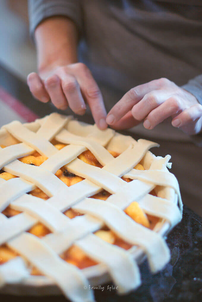 Crimping edges of lattice top peach blueberry pie in a pie dish by FamilySpice.com