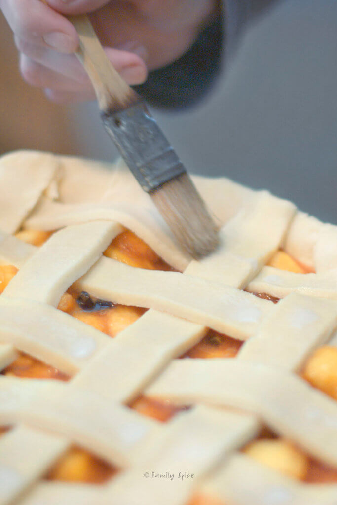 Closeup of brushing sugar milk onto the lattice top and crust of an unbaked blueberry peach pie