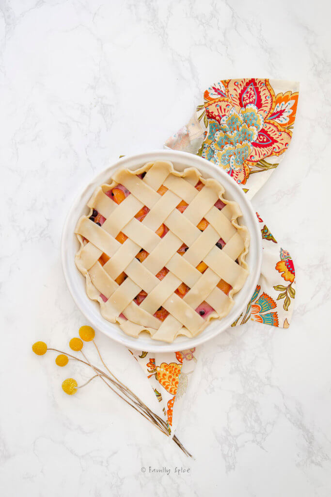 Top view of an unbaked blueberry peach pie with a lattice top