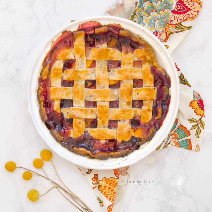 Top view of a blueberry peach pie baked and bubbly with a lattice top