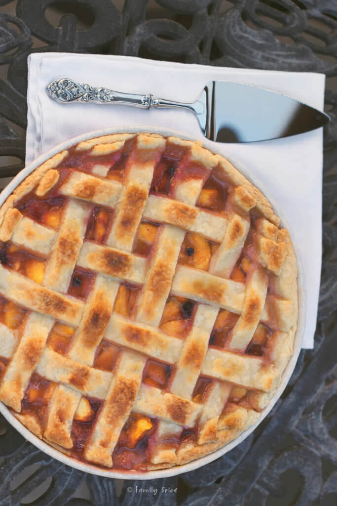 Top view of a baked blueberry peach pie with a lattice top