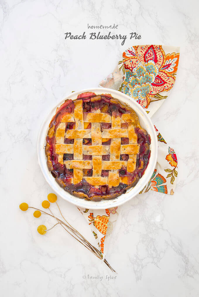 Overhead shot of a bubbly baked peach blueberry pie with lattice top by FamilySpice.com