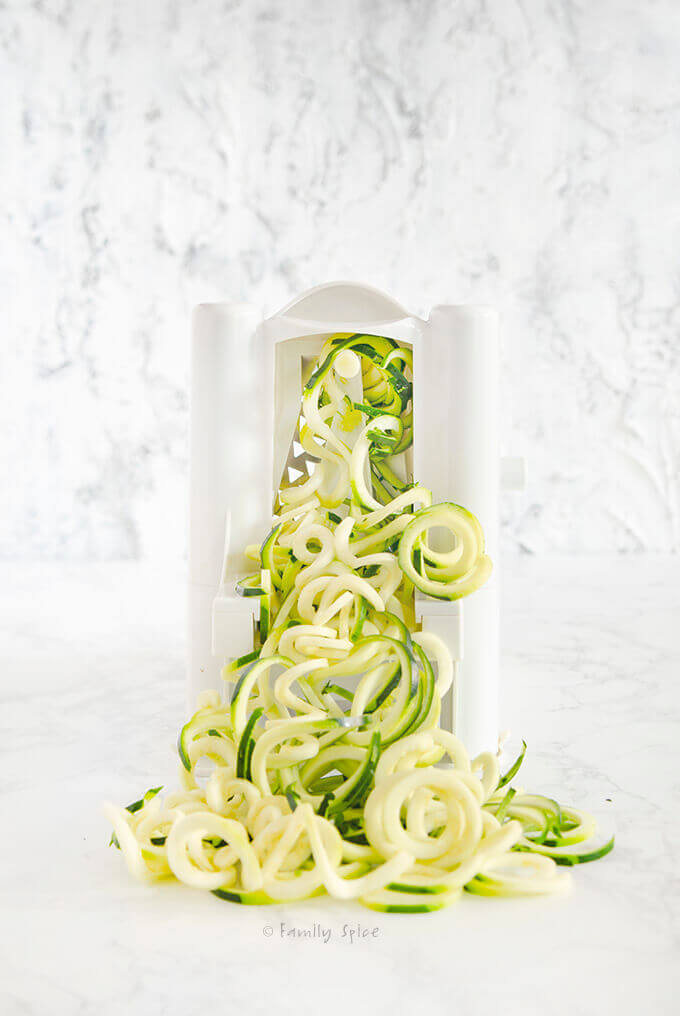 Side shot of spiralizing zucchini by FamilySpice.com