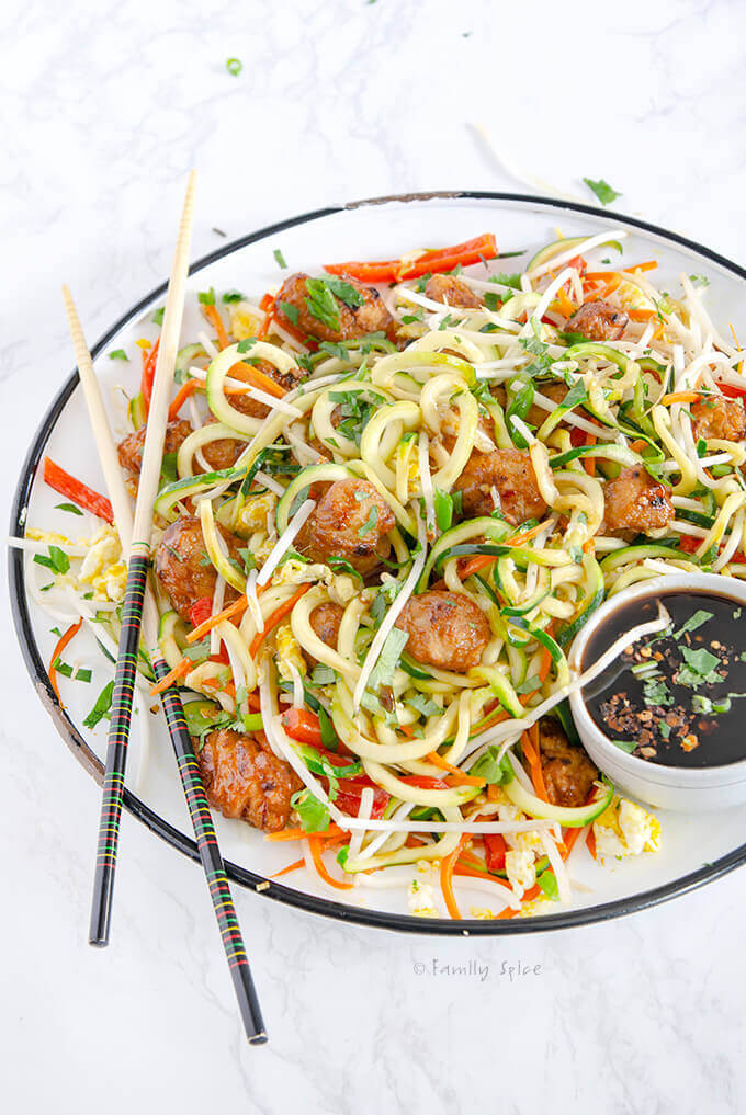 Closeup of a plate full of Zucchini Noodle Pad Thai with Orange Chicken by FamilySpice.com