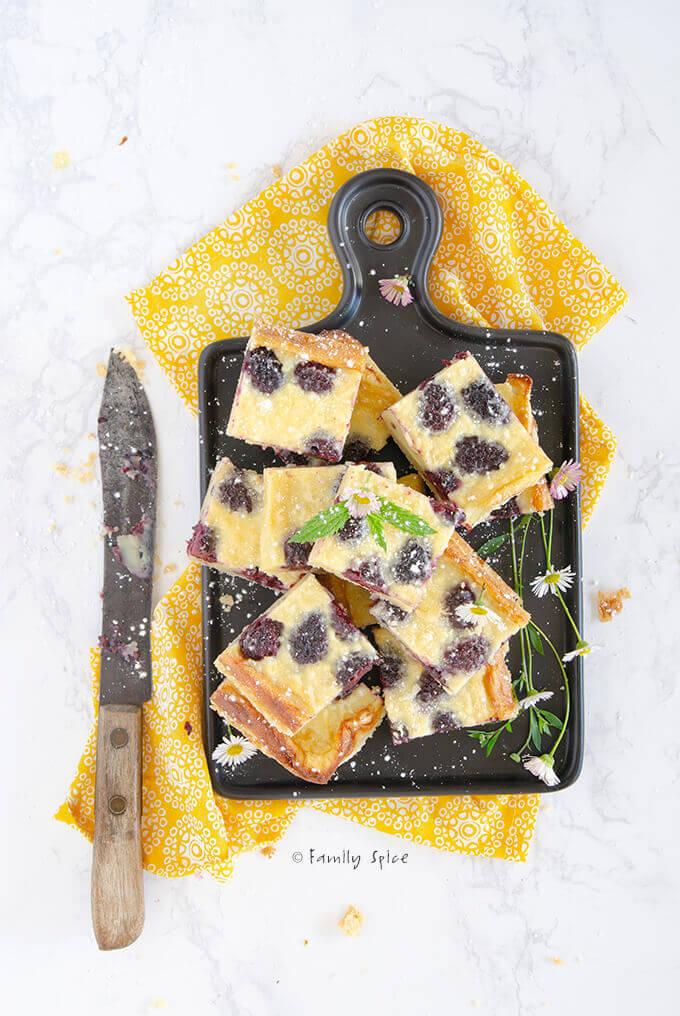 Overhead shot of blackberry custard bars on a black cutting board with knife by FamilySpice.com