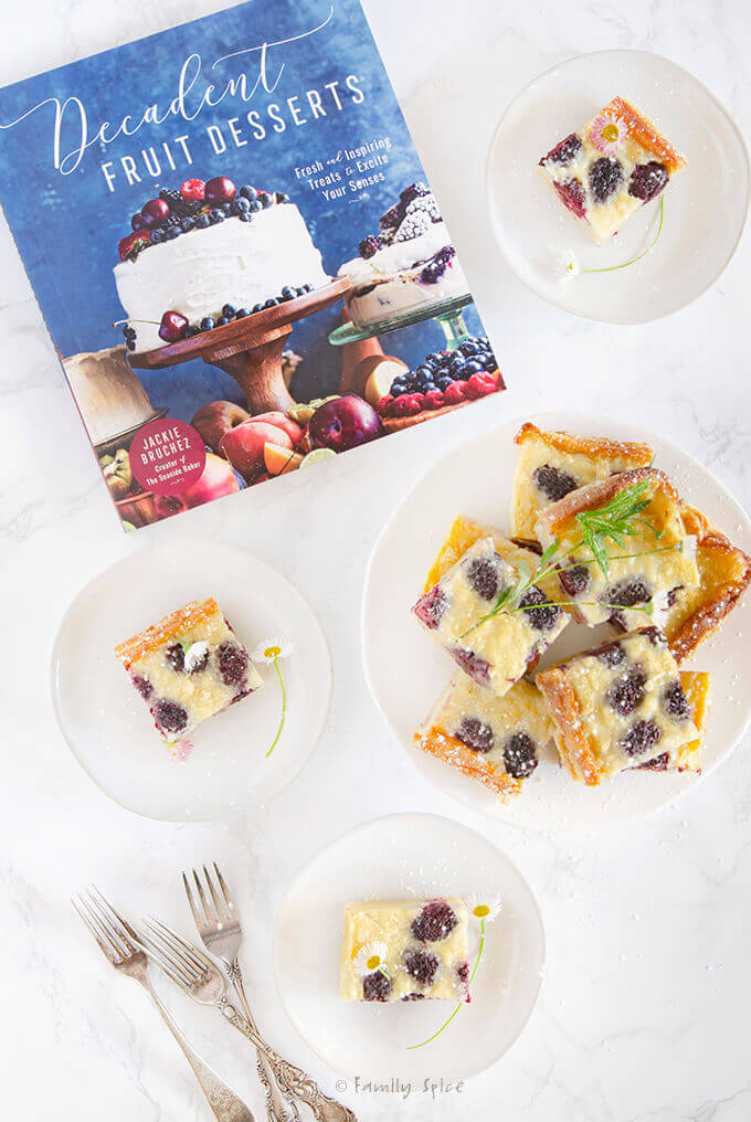 Overhead shot of a Decadent Fruit Desserts cookbook and blackberry custard bars by FamilySpice.com