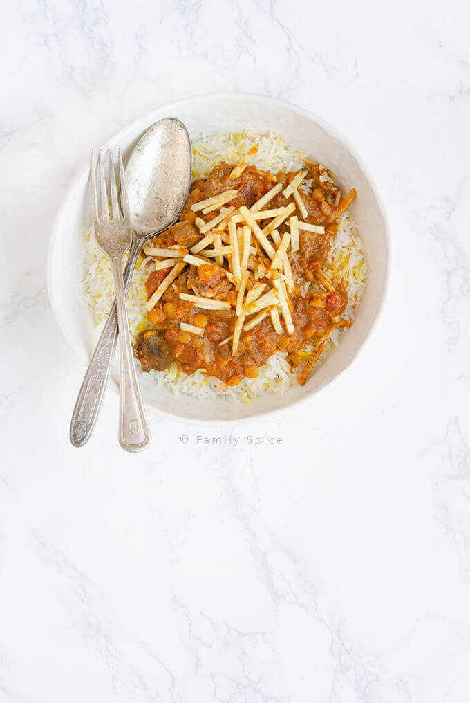 A bowl of basmati rice topped with Khoresh Gheymeh (Persian Split Pea Stew) and shoestring potatoes by FamilySpice.com