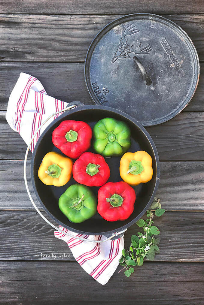 Overhead view of a cast iron Dutch oven filled with colorful bell peppers by FamilySpice.com