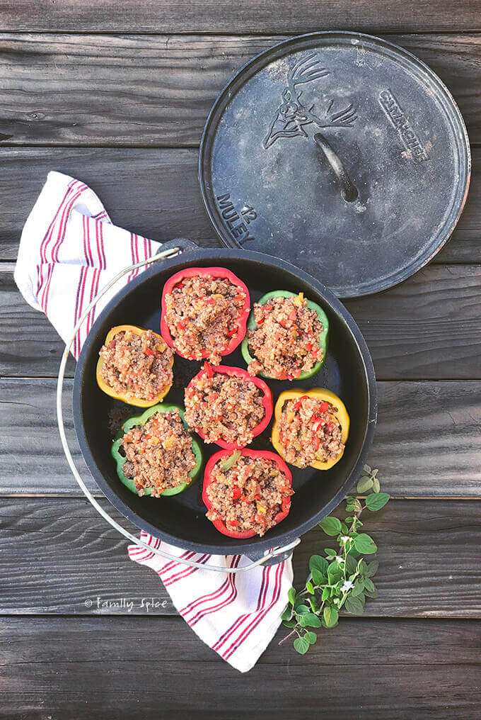 Overhead view of a cast iron Dutch oven filled with colorful bell peppers stuffed with Italian seasoned meat stuffing by FamilySpice.com