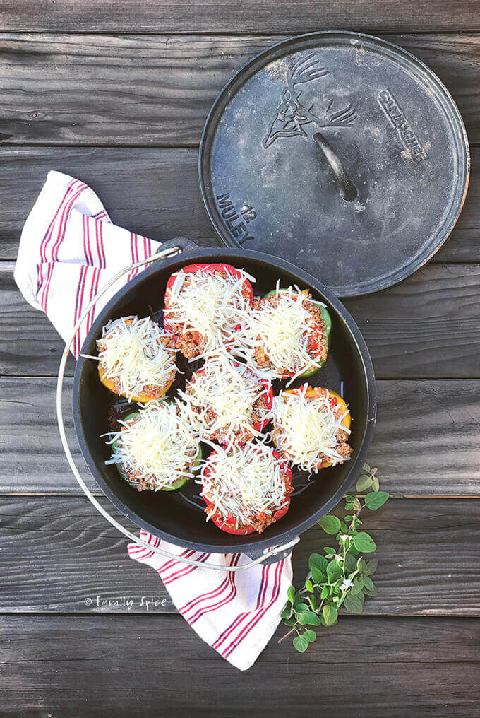 Overhead view of a cast iron Dutch oven filled with Italian stuffed bell peppers topped with cheese by FamilySpice.com