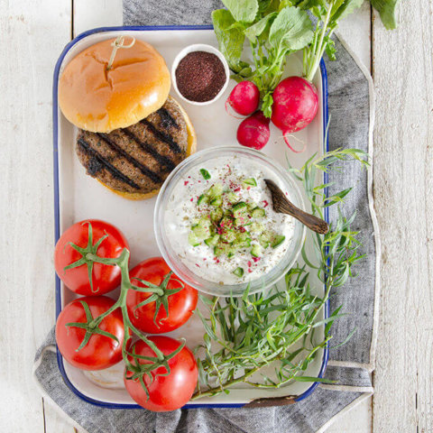 A tray full of vegetables and yogurt to accompany a grilled Persian kabab burger