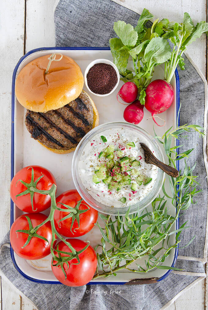 Closeup of a tray filled with herbs, tomatoes, radishes, yogurt and a Persian kabab burger by FamilySpice.com
