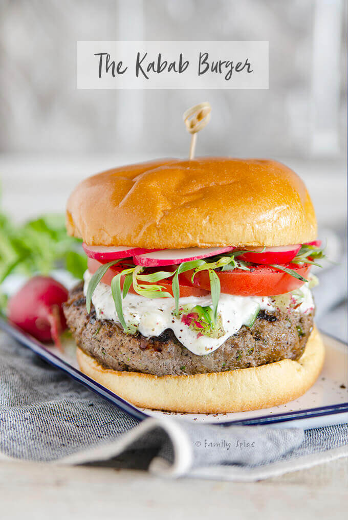 Closeup of a grilled Persian kabab burger topped with yogurt, tomatoes, radishes and tarragon by FamilySpice.com