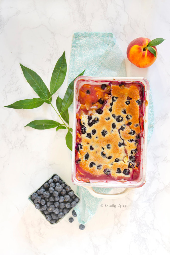 Top view of a peach blueberry cobbler with a corner of the biscuit topping removed