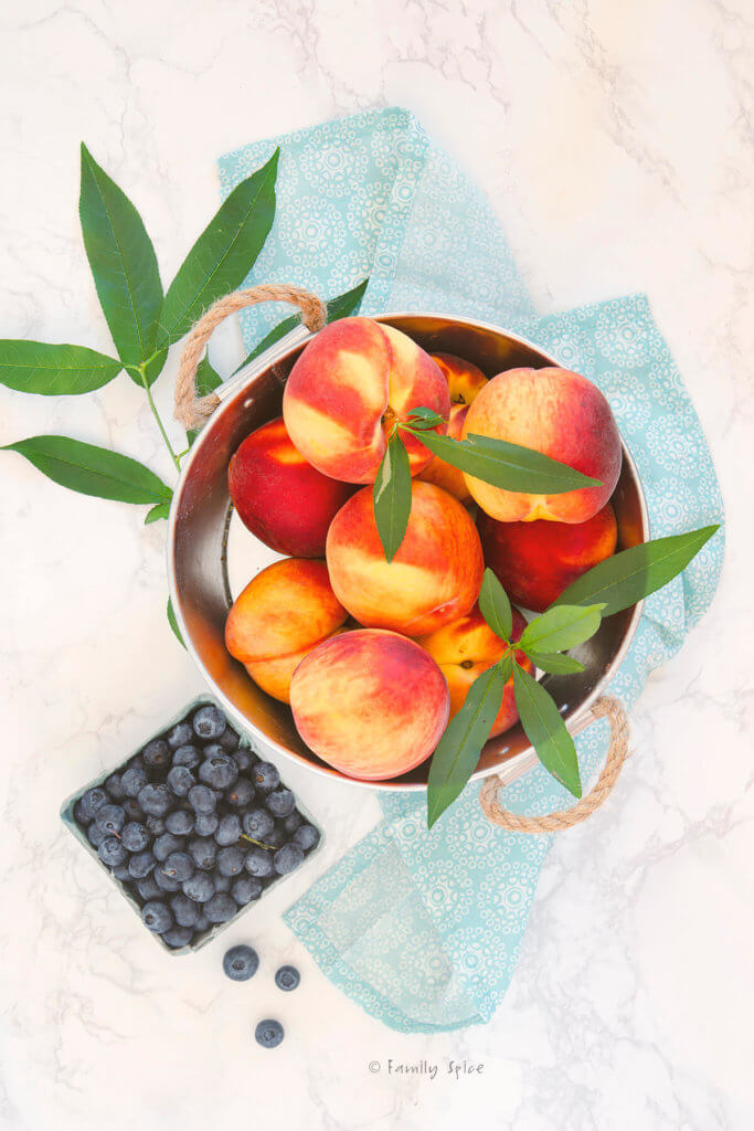 Fresh peaches in a metal bin with blueberries next to it