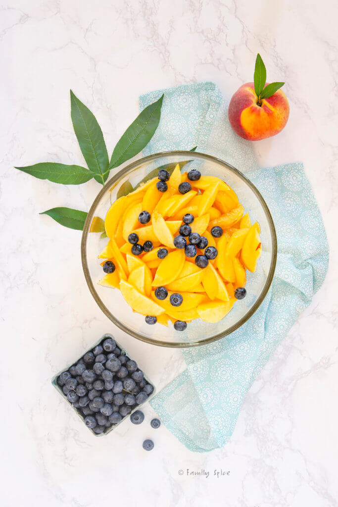Blueberries and peach slices in a mixing bowl