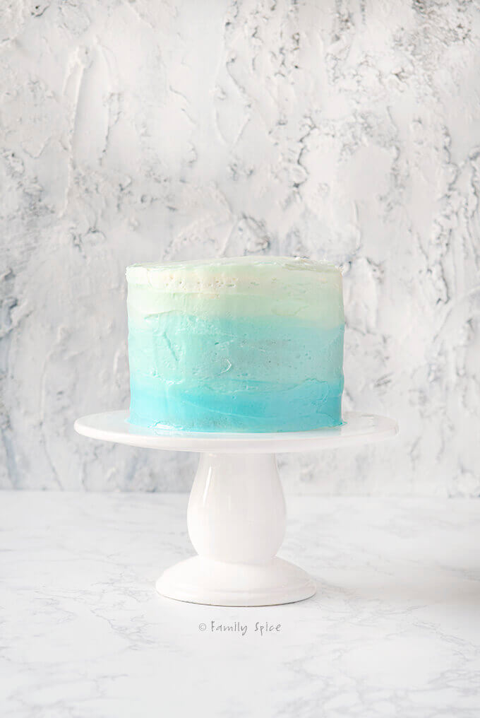 Frosted blue raspberry kool aid ombre cake on a white cake pedestal by FamilySpice.com