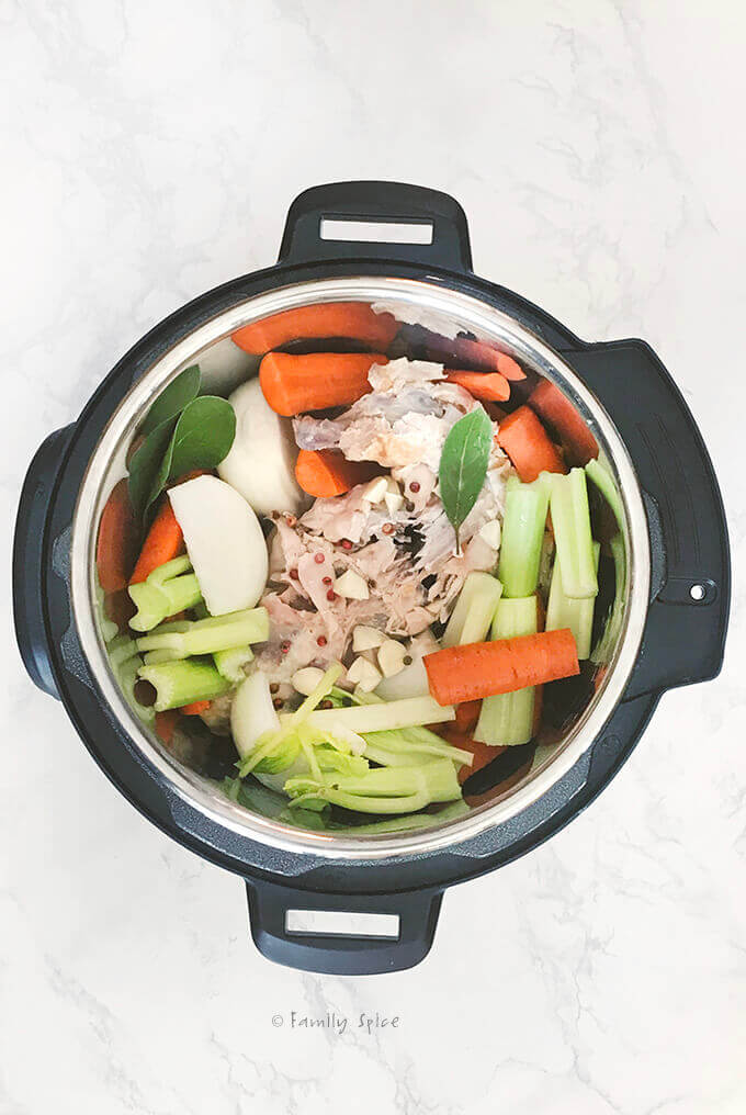 Adding vegetables to chicken bones to make bone broth in the instant pot by FamilySpice.com