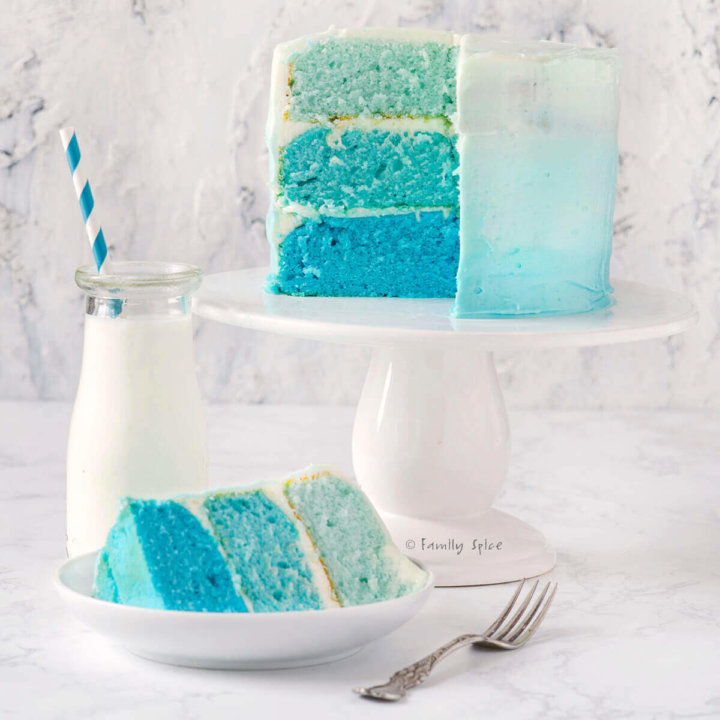 Frosted blue raspberry kool aid ombre cake with a slice cut out and a bottle of milk by FamilySpice.com